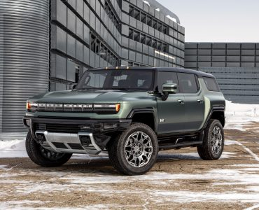 A DARK GREEN HUMMER EV IS PARKED IN A DIRT LOT DUSTED WITH SNOW NEXT TO A MODERN WAREHOUSE STRUCTURE.